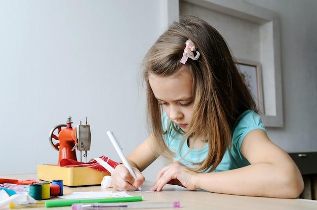 La niña está dibujando un boceto de un vestido para una muñeca.