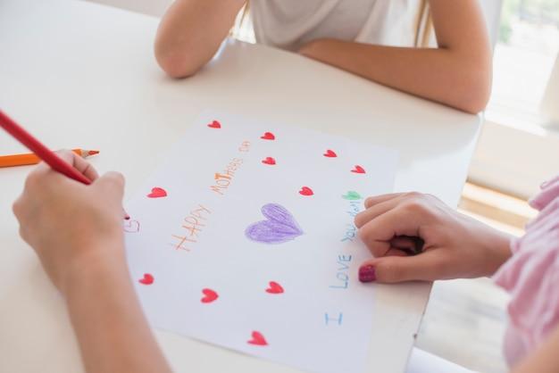 Niña dibujando corazones en papel con la inscripción del día de la madre feliz