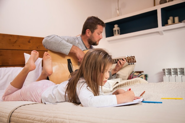 Niña dibujando mientras su padre toca la guitarra