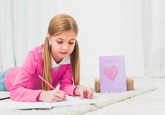 Niña, dibujo, en, papel, cerca, tarjeta de felicitación