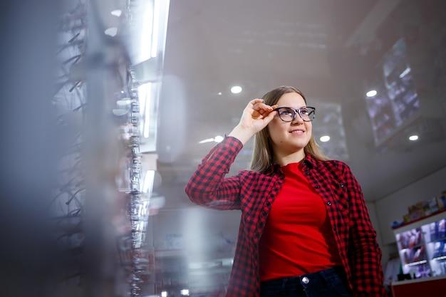 Una niña con discapacidad visual elige gafas. lleva una camisa y una hermosa sonrisa.