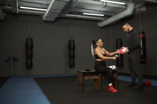 Una niña discapacitada participa en el gimnasio. una mujer con una pierna entrena con un entrenador de boxeo, aprende a pelear