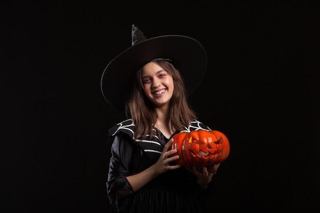 Niña en un disfraz de bruja haciendo brujería en una calabaza aterradora. niño feliz en un disfraz de bruja para halloween.