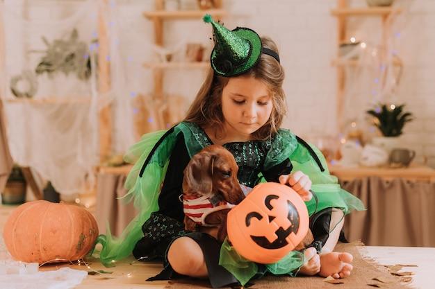 Niña en un disfraz de carnaval de halloween y un perro salchicha están sentados en la cocina