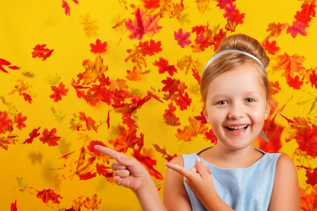 Niña con un disfraz de princesa sobre un fondo de hojas de otoño cayendo