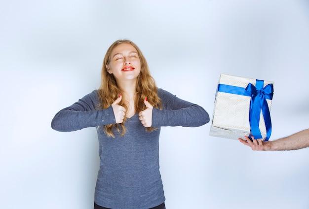 La niña disfruta de la caja de regalo azul blanca que se le ofrece.