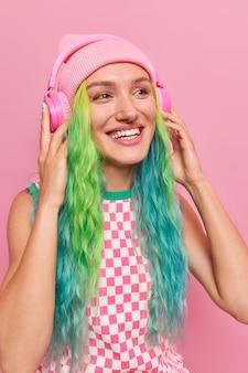 Niña disfruta de la pista de audio en auriculares inalámbricos escalofríos en el interior escucha música con sonido fuerte tiene el pelo teñido de colores viste sombrero y vestido a cuadros aislado en rosa