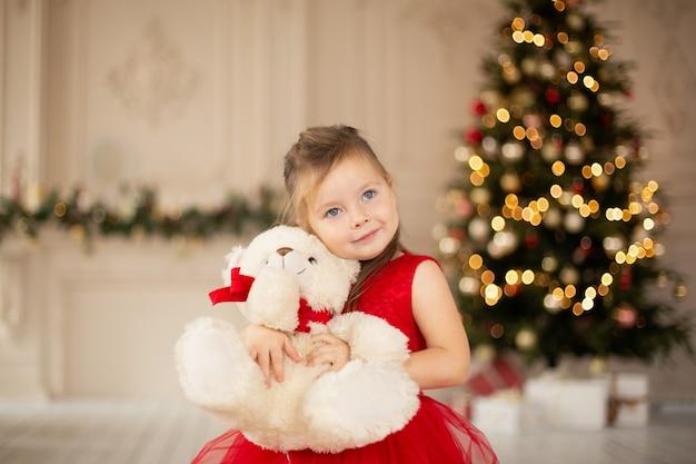 Una niña disfruta de su nuevo osito de peluche regalado por santa claus para navidad.