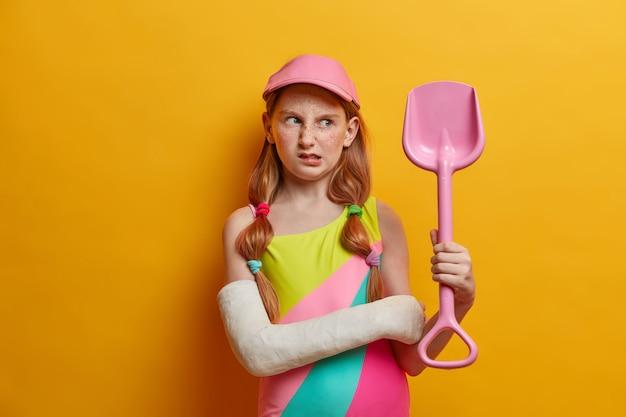 Una niña disgustada con cabello rojo y pecas mira con tristeza la pala de arena, ha echado a perder las vacaciones de verano debido a un trauma, posa con el brazo roto, necesita un tratamiento prolongado, usa yeso