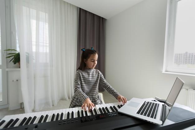 Niña a distancia aprendiendo el piano en línea durante la cuarentena. concepto de coronavirus.