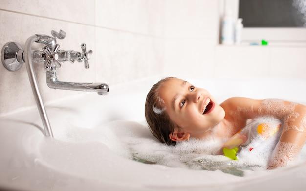 Niña divertida se baña en una bañera con un salvavidas inflable y con espuma en el agua