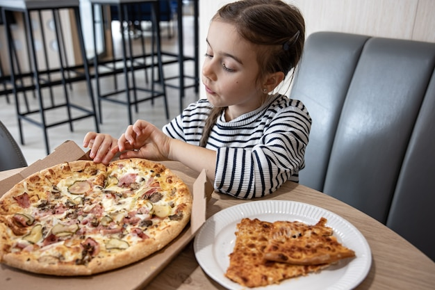 Niña divertida comiendo pizza en una caja de cartón para el almuerzo.