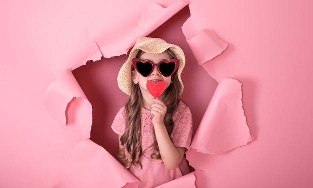 Niña divertida con un corazón en un palo en una pared de color