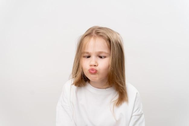 Niña divertida hace muecas sobre un fondo blanco. infancia feliz. vitaminas y medicinas para el niño.