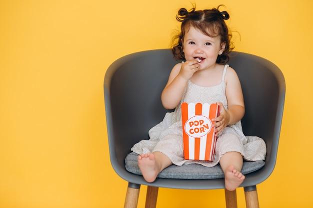 Niña divertida sonriendo y sentada en una silla en casa comiendo palomitas de maíz y viendo una película