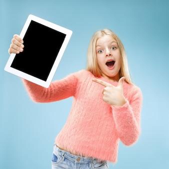 Niña divertida con tableta en estudio azul. ella muestra algo y apunta a la pantalla.