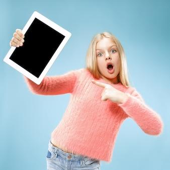 Niña divertida con tableta sobre fondo azul de estudio. ella muestra algo y apunta a la pantalla.