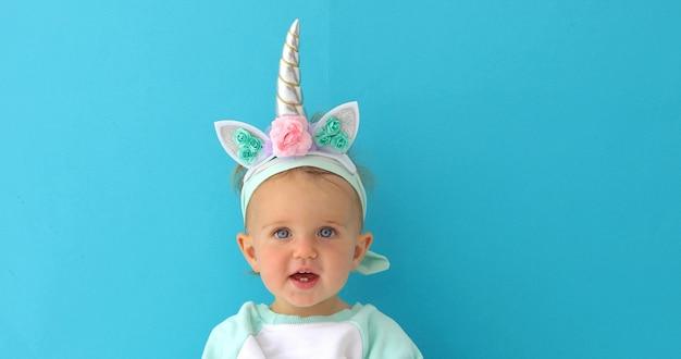 Niña divertida del unicornio en fondo azul