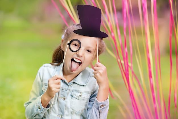 Niña con divertidos vasos de papel y sombrero