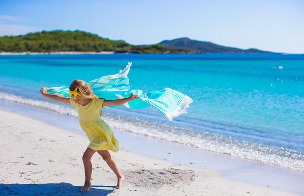Niña divertirse con una toalla de playa durante las vacaciones tropicales