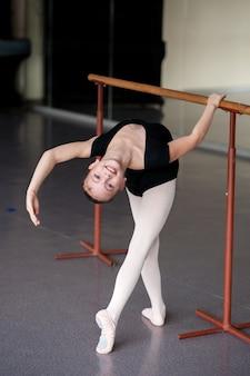 La niña se dobla en la lección de coreografía.