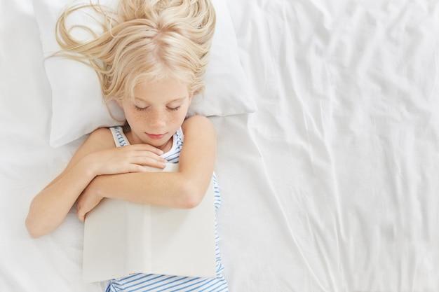 Niña dormida con largo cabello rubio, manteniendo el libro en las manos, durmiendo después de leer cuentos de fantasía o de hadas, teniendo sueños agradables. niño descansando en una habitación cómoda después de jugar activamente con amigos