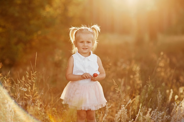 Niña con dos colas. lindo bebé en una falda rosa. la niña camina en el parque al atardecer