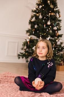 Niña elegante con una bola brillante y se sienta cerca del árbol de navidad