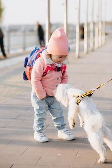 Niña elegante feliz en una chaqueta de mezclilla rosa con un perro blanco en el parque