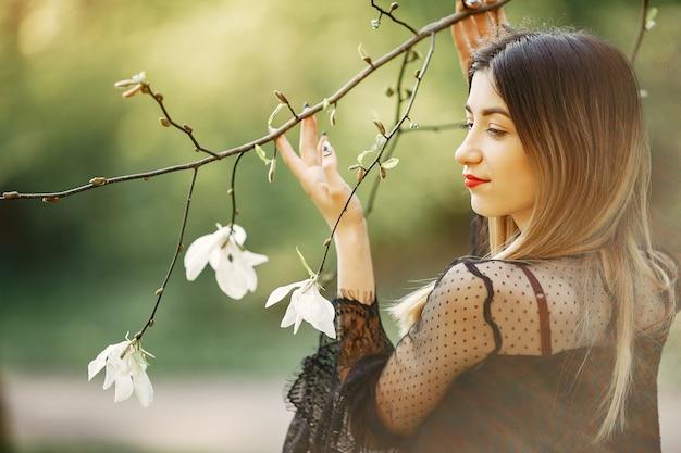 Niña elegante en un parque de primavera