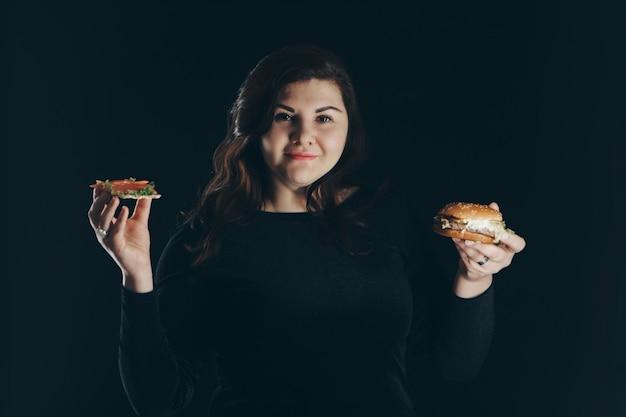 La niña elige entre comida sana y deliciosa. un bocadillo de pescado y una hamburguesa en manos de una mujer. aislado en un fondo negro. copia espacio