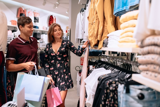 Una niña elige la ropa, junto a ella hay un joven con paquetes en la mano. compras.