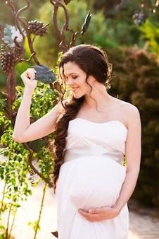 Una niña embarazada feliz en un vestido blanco está caminando en el parque.
