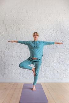 Niña embarazada en un traje deportivo azul se encuentra en pose de yoga, retrato de cuerpo entero