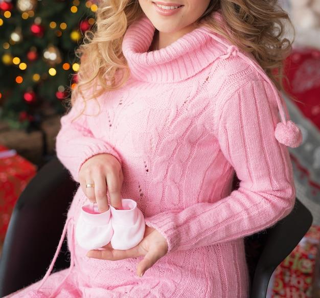 Niña embarazada en la víspera de navidad en casa cerca del árbol de año nuevo