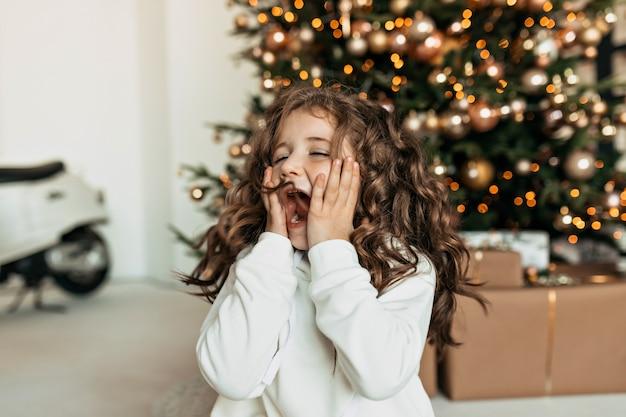 Niña emocionada con emociones sorprendidas que cubren la cara con las manos sentadas frente al árbol de navidad y esperando los regalos de navidad