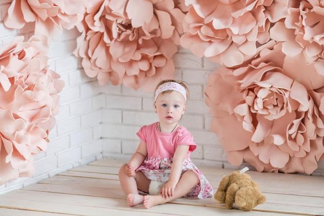 Niña en vestido rosa se sienta entre grandes flores de papel rosa
