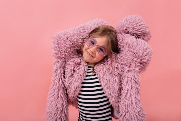 Niña encantadora con abrigo de piel de moda y gafas redondas está levantando las manos y sonriendo