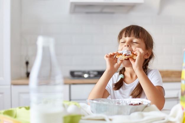 Niña encantadora y hambrienta de cabello oscuro que muerde y disfruta de un croissant, mantiene los ojos cerrados, se sienta a la mesa en la cocina y prueba los deliciosos pasteles hechos por su encantadora madre.