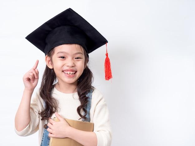 Niña encantadora preescolar de 6 años con sombrero de graduación y sosteniendo un libro sobre las manos en la pared blanca.