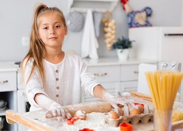 Niña encantadora con rodillo de cocina