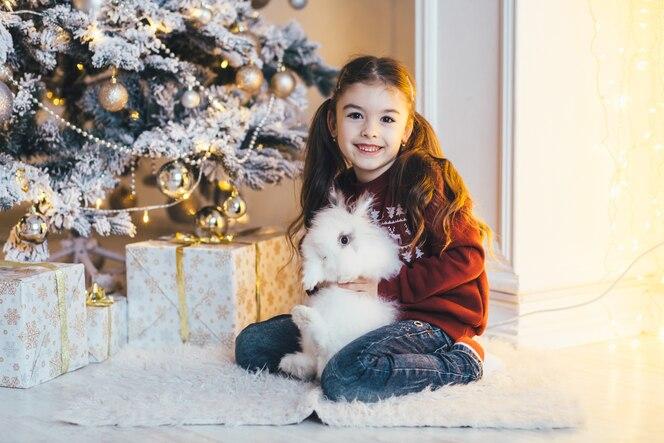 Niña encantadora se sienta con un conejo antes de un brillante árbol de navidad