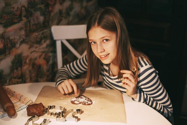 Una niña encantadora y sonriente en la cocina de la casa, en la mesa, cortó galletas con forma de corazón de la masa