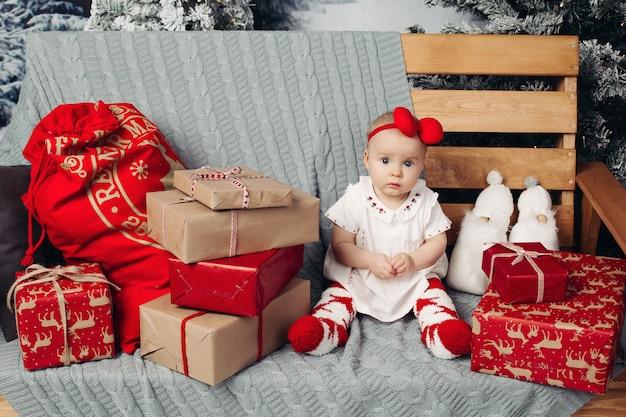 Niña encantadora sonriente en lindo vestido con diadema sentado en el banco con muchos regalos de navidad