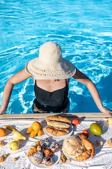 Una niña se encuentra en el agua azul clara en la piscina con un delicioso desayuno.
