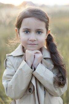 Una niña se encuentra en un campo. manos dobladas concepto de paz, esperanza, sueños,