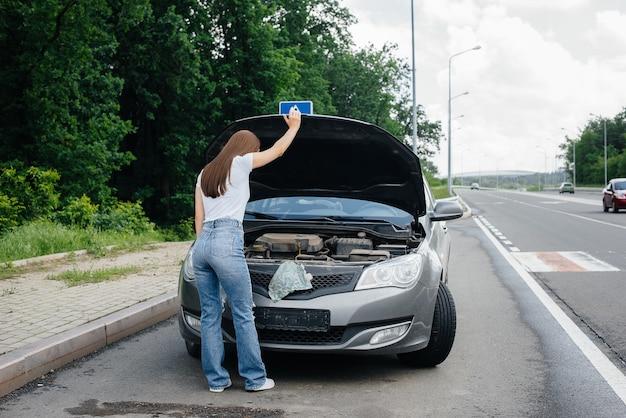 Una niña se encuentra cerca de un automóvil averiado en medio de la carretera y mira debajo del capó. avería y avería del coche. esperando ayuda.