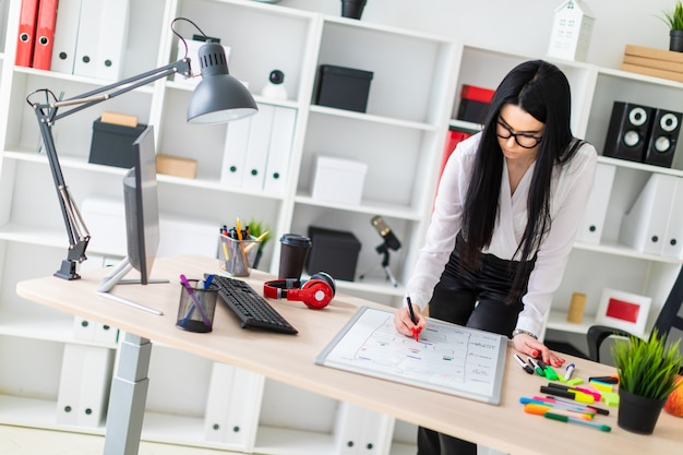 Una niña se encuentra cerca del escritorio de una computadora y dibuja un marcador en una pizarra magnética.