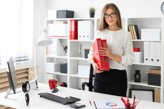 Una niña se encuentra cerca de una mesa en la oficina y sostiene una carpeta con documentos.