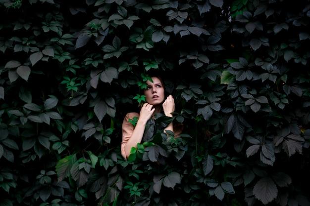 Niña se encuentra en hojas verdes a solas con la naturaleza, una mujer toca plantas y sueños, un concepto de un hombre en la naturaleza